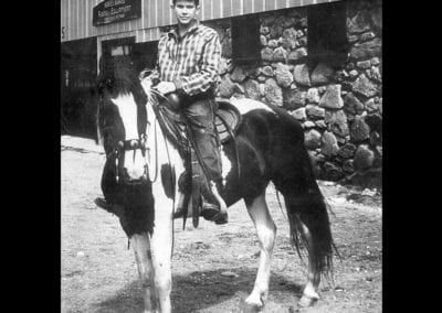 Owen the founder of Box Lunch, pictured as a teenager riding a horse
