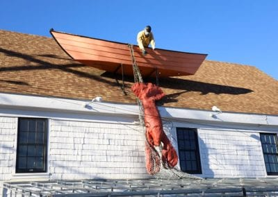 boat mounted on a roof in Wellfleet with man reaching outside of boat out to a large lobster